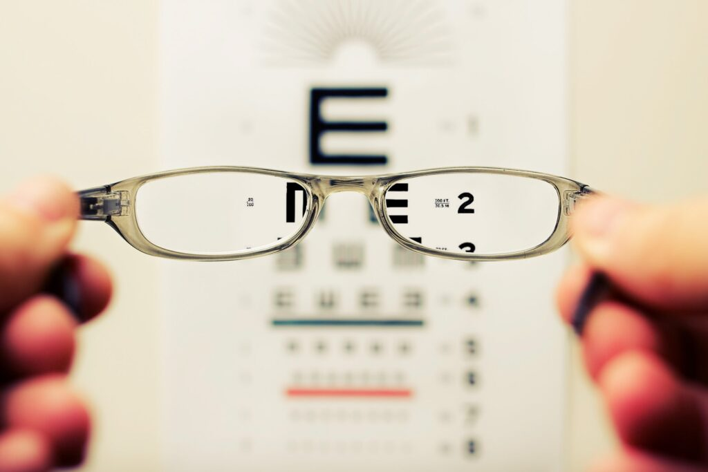 pair of glasses, with eye-test board behind it.
